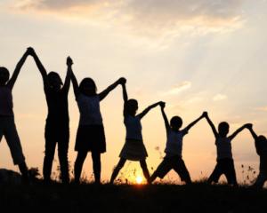 Kids holding hands, sunset