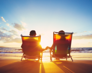 couple holding hands sitting on beach
