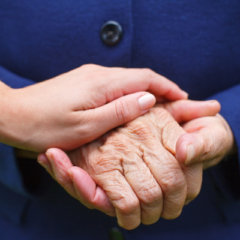 woman and elderly woman holding hands